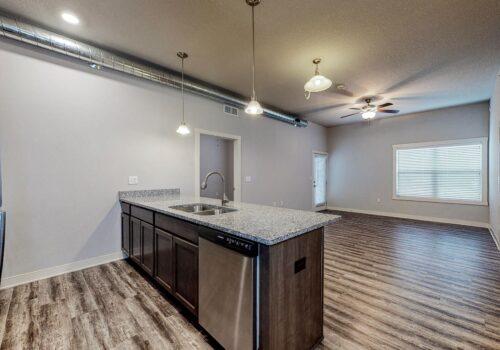 uptown lofts kitchen across counter to living area and second bedroom doorway