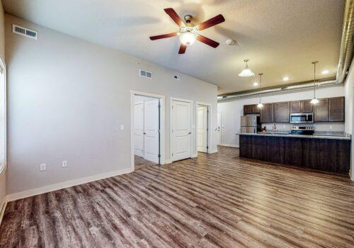 uptown lofts living area looking at open kitchen and doorway to main bedroom