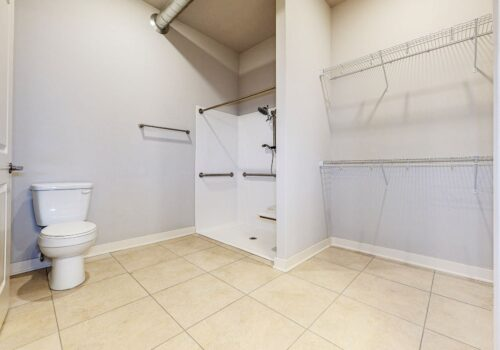 uptown lofts main bathroom with open closet storage toilet and mobility accessible shower